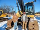 Ron Nornberg (L) of Little Falls, Minn., stands  with Jim Kimman, owner of Kimman's Dirt Diggers, Little Falls, Minn. Kimman said he bought a truck and is looking to purchase more equipment like this  John Deere 350D excavator.